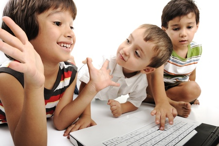 Group of children playing on white laptop together. Isolated on white. Stock Photo - 8799381