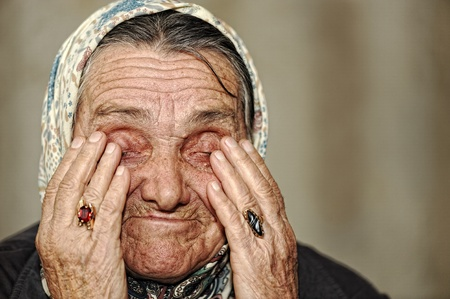 Mature woman crying with hands on her face photo