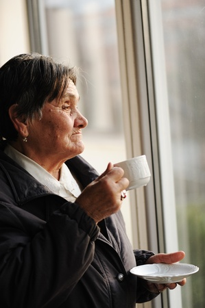 Portrait of Senior Woman Looking Through Window and Drinking a Cup of Coffee photo