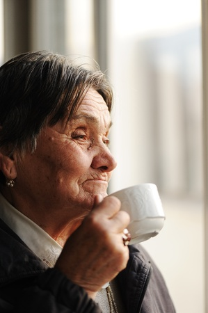 Portrait of Senior Woman Looking Through Window and Drinking Coffee photo