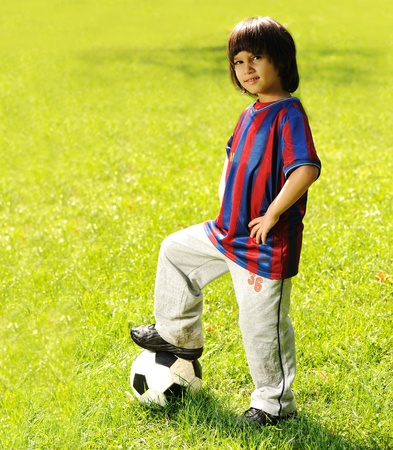 happy kid playing football in a park outdoors photo