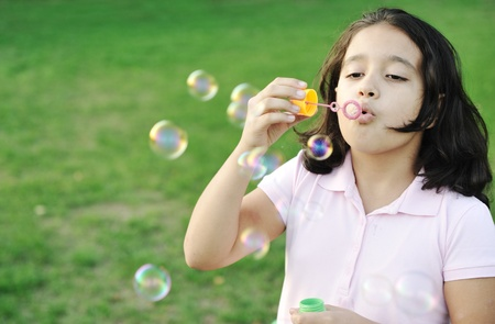 Girl blowing bubbles outdoor photo