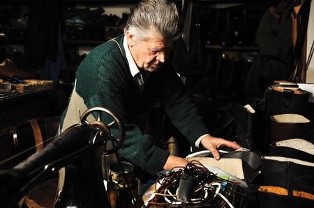 tienda de zapatos: Senior hombre trabajando con una m�quina antigua en su propio taller Foto de archivo