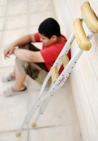 wees:  Kid zittend op de straat met een krukken