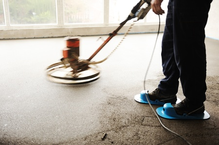 leveling: Equating and leveling fresh cement for the floor, by one worker Stock Photo