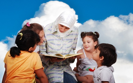 A young muslim woman in traditional clothes in education process photo