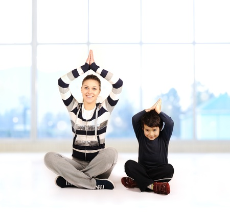 Family - young woman and kid - doing yoga exercises indoors photo