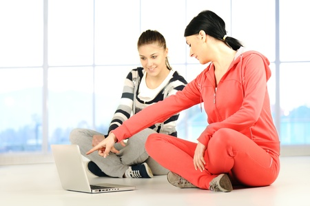 Two girls doing yoga and fitness using laptop in bautiful bright surround  photo