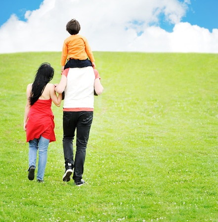 walk in: Young family having a walk in the sun over the meadow on a bright summer day Stock Photo