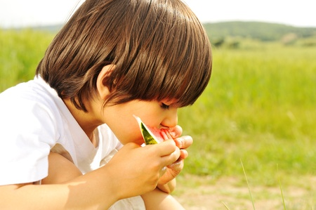 cute little boy eating watermelon on the grass in summertime photo