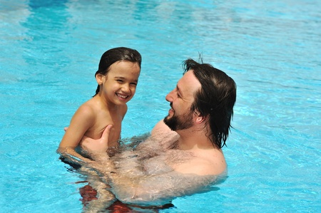 Happy father with his son in pool photo