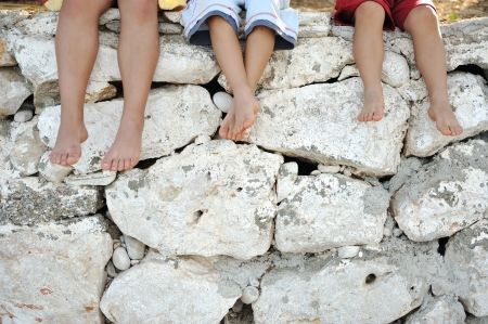 man feet: Children sitting on wall, happy boys laughing Stock Photo