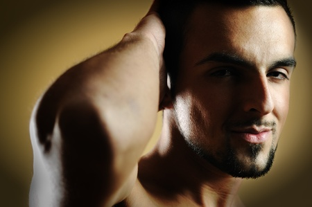 the tempter: handsome  man posing against dark background Stock Photo