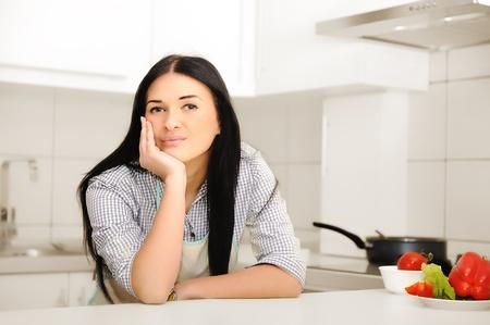 new thinking: Beautiful woman thinking in kitchen Stock Photo
