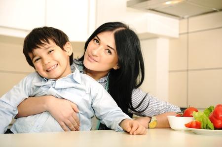 mama e hijo: Madre feliz y peque�o hijo en la cocina, feliz y fraternidad Foto de archivo