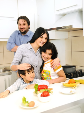 Happy family of four members in kitchen photo