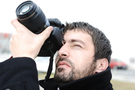 Young professional man with camera shooting outdoor photo