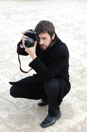 paparazzi: Young professional man with camera shooting outdoor