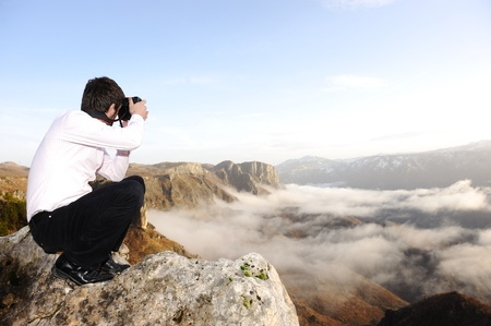 Young professional man with camera shooting outdoor, fantastic landscape photo