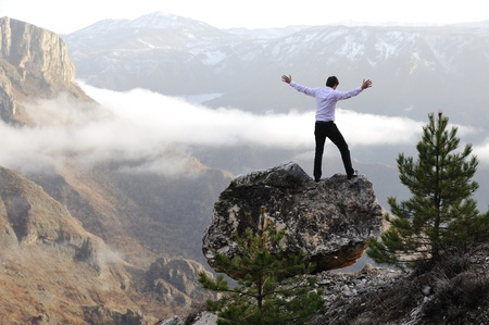 Man on top of mountain with open arms. Conceptual design. photo