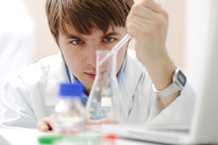 medical scientist: Young medical scientist working in modern lab, research with tubes and notebook