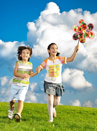 Fantastic scene of happy children running and playing carefreely on green meadow in nature photo