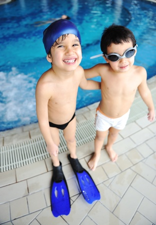 kids swimming: Activities at the pool, children swimming and playing in water, happiness and summertime