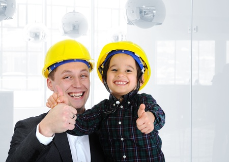 executive helmet: Happy boss and employee together, father and son engineers on work playing Stock Photo