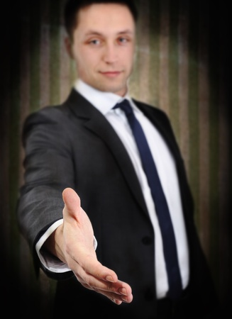 Successful young man extending hand to shake, on grunge vintage wall background photo