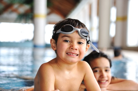 Happy young children, boy and girl, relaxing on the side of a swimming pool wearing blue and pink goggles and snorkel photo