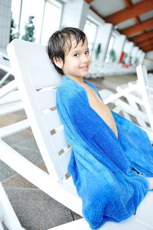 beach towel: Young boy laying on towel by the edge of the pool Stock Photo