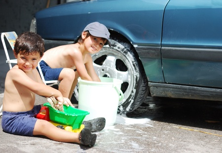 Playing around the car and cleaning, children in summertime photo