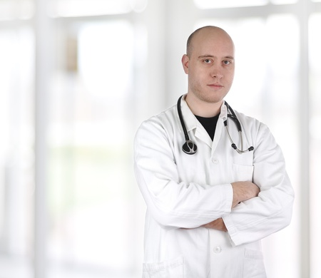 folded arms: Smiling confident doctor standing with hands crossed isolated on white background, bald Stock Photo