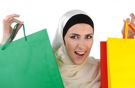 compras compulsivas: Hermosa tradicional pero moderna mujer musulmana sosteniendo bolsas de compras