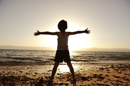 Silhouette of child on the beach, holding his hands up, towards the sun photo