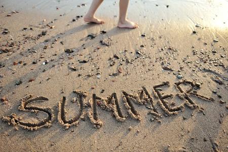summer season: the word summer written in sand
