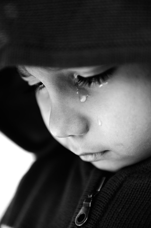 Kid crying, focus on his tear, added a bit of grain, black and white Stock Photo