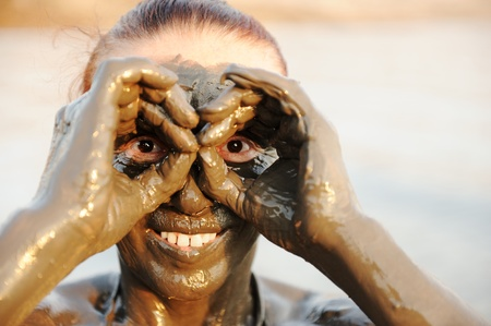 sourced: A woman enjoying the natural mineral mud on face sourced from the dead sea in background