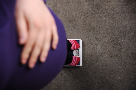 Pregnant woman weighing on scale photo