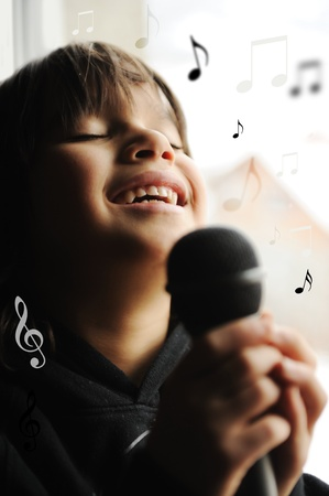 Kid singing, with black microphone photo