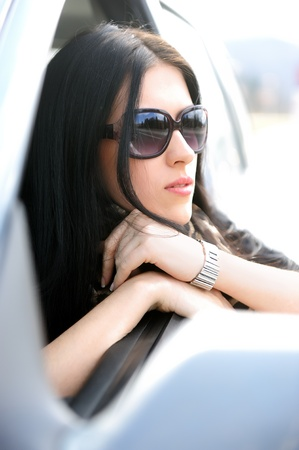 Beautiful attractive woman in car, looking through the window photo