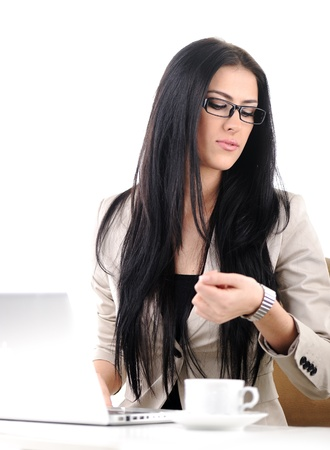 Office portrait of beautiful young business woman looking at her wrist watch photo
