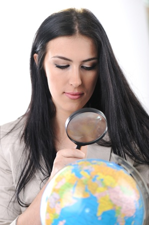 Young beautiful woman with magnifier searching on Earth map, globe photo