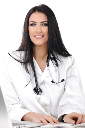 Young doctor woman looking to camera with smile, sitting on her desk photo