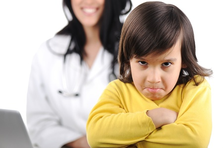 attitude boy: Young female doctor examining little cute angry child refusing examining