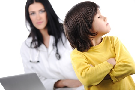 Young female doctor examining little cute angry child refusing examining photo