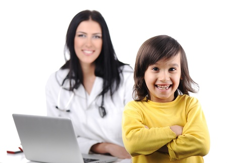 Young female doctor examining little cute child at modern hospital photo