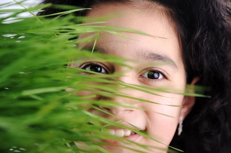 Girl and grass, happy face behind green color photo