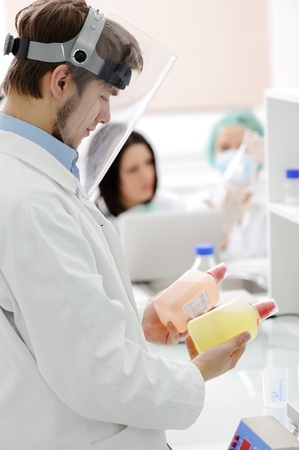 group of the students working at the laboratory with liquids in bottles photo