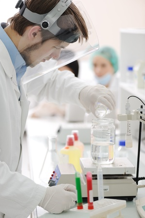 Group of the students working at the laboratory with liquids in tubes and electronics Stock Photo - 10087137